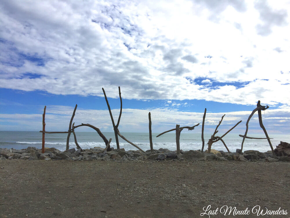 Sign made out of driftwood that spells out the word 'Hokitika'. It's standing up on the water's edge looking out to the ocean