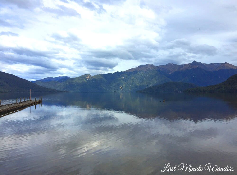 Reflective lake with mountains and clouds and a jetty on the left