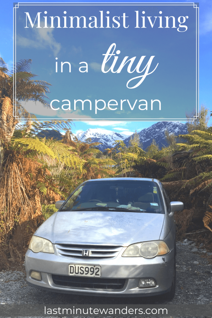 Silver car parked on gravel surrounded by tree ferns with mountains in background and text overlay - Minimalist living in a tiny campervan
