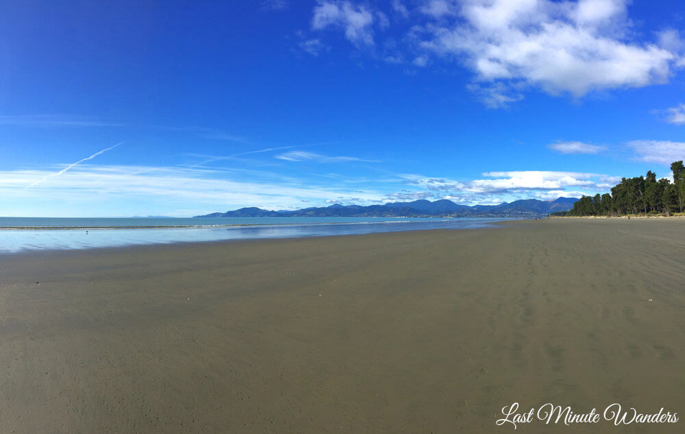 Wide sand beach with mountains in distance
