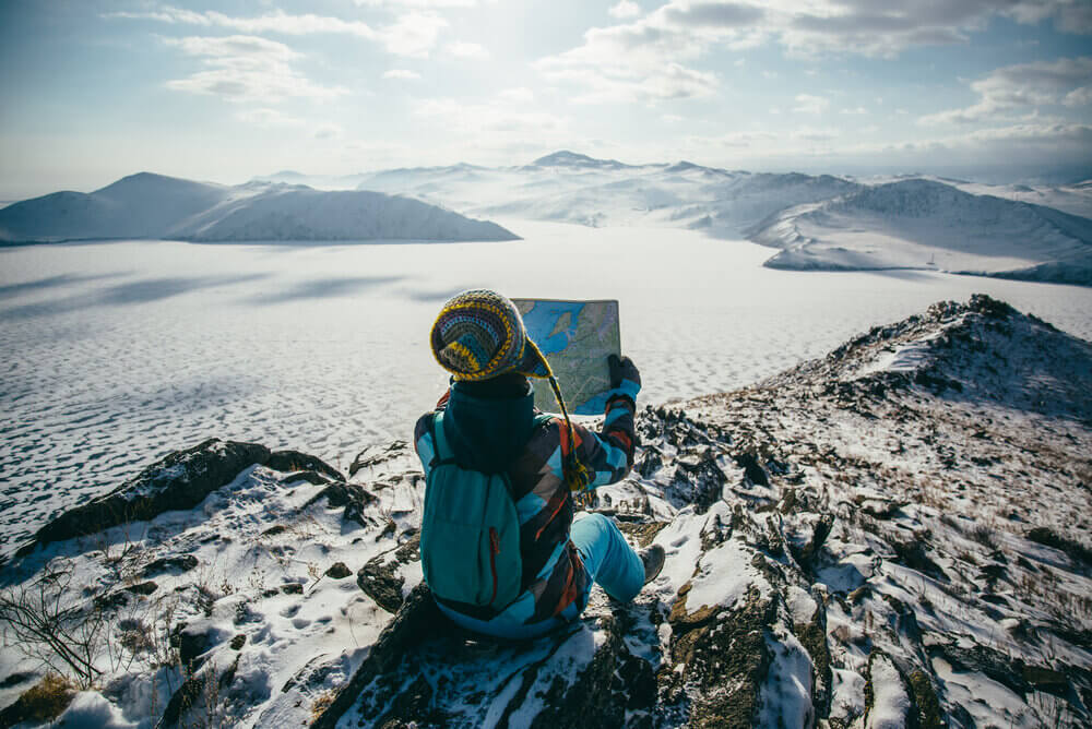Person sat on snowy mountain overlooking a frozen landscape while studying a map